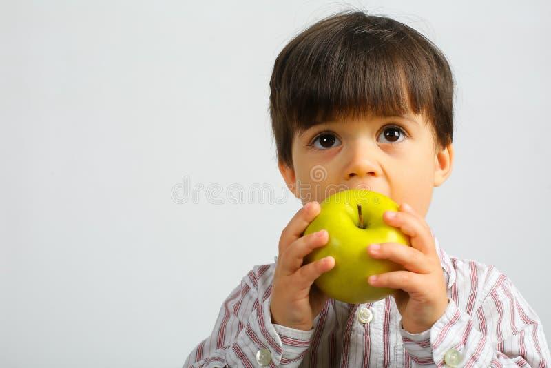 Joli petit gar?on mangeant la pomme verte photos stock