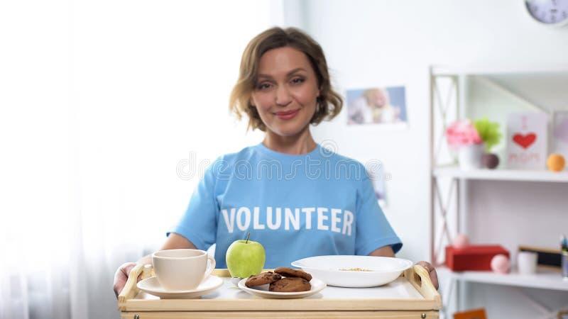 Joli plateau de sourire de participation d'assistant social avec la nourriture de petit déjeuner dans des mains, gentillesse photographie stock libre de droits