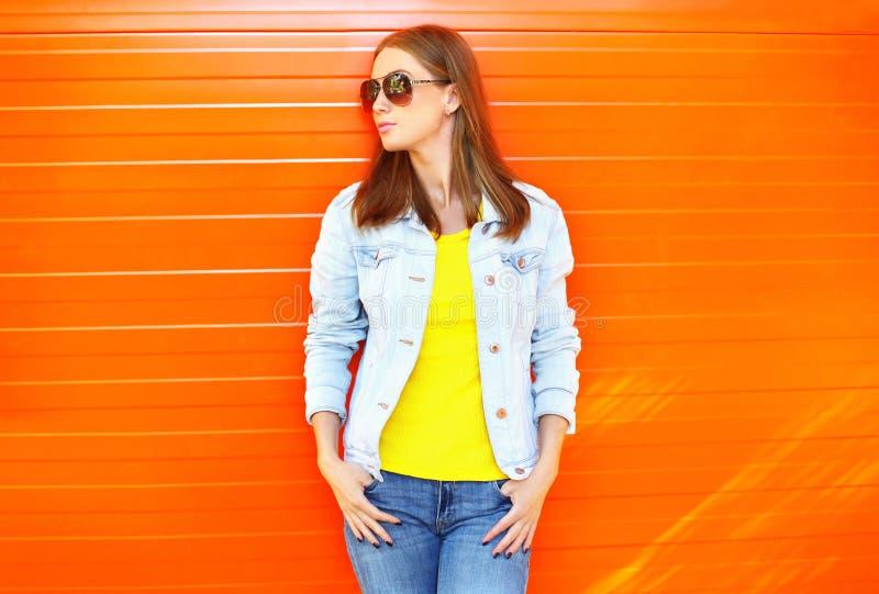 Joli port de femme lunettes de soleil et veste de jeans dans le profil au-dessus du fond orange image stock