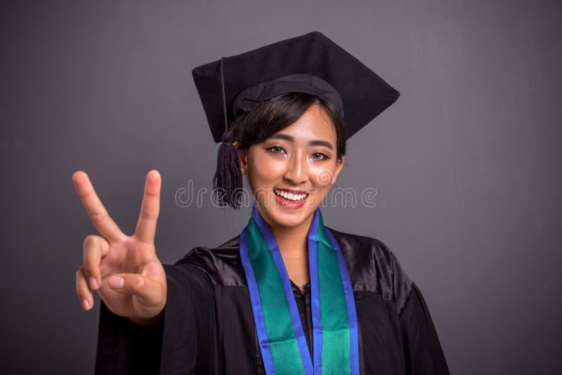 Joli portrait de plan rapproché d'obtention du diplôme de signe de paix d'étudiant image libre de droits