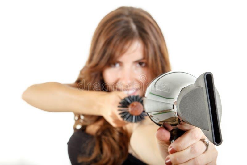 Joli styliste en coiffure tenant le hairdryer et la brosse à cheveux photographie stock libre de droits