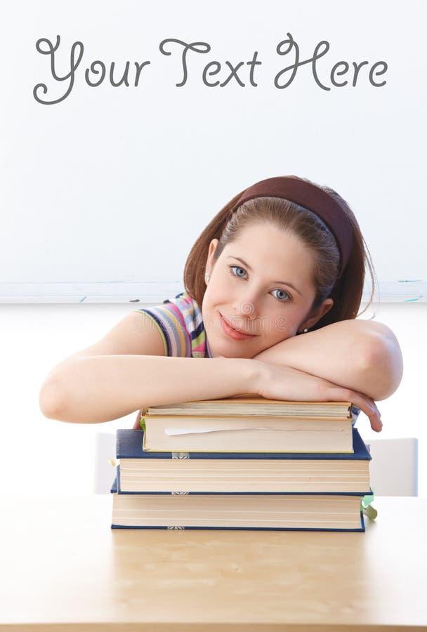 Jolie écolière s'étendant sur des livres dans la salle de classe images libres de droits