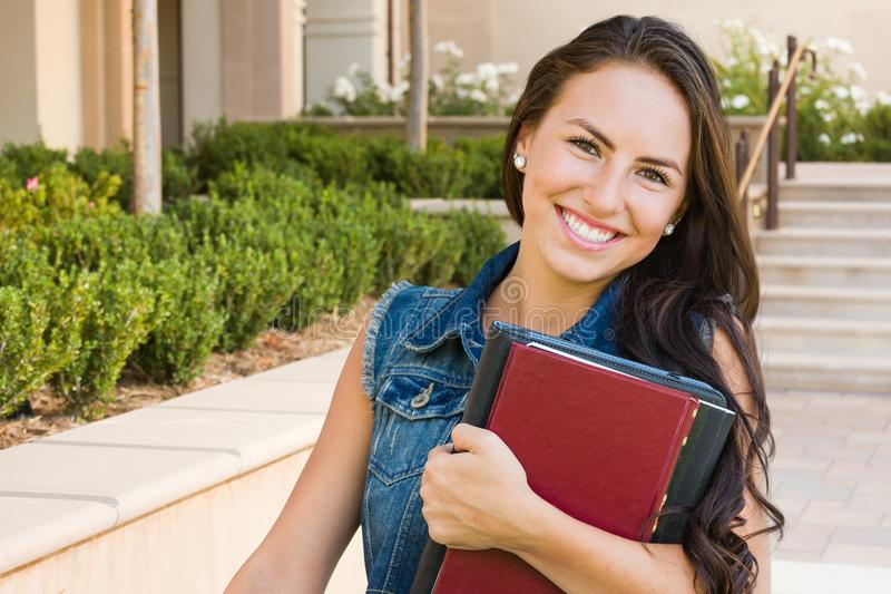 Jolie étudiante de métis avec des livres d'école sur le campus photo libre de droits