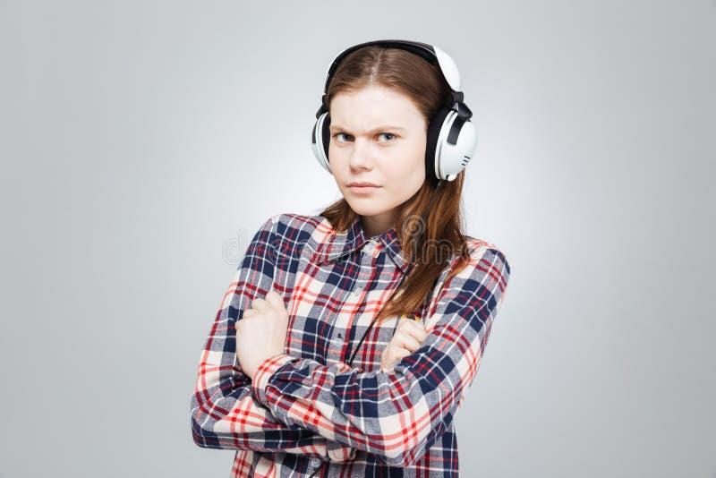 Jolie adolescente sérieuse écoutant la musique dans des écouteurs photos libres de droits