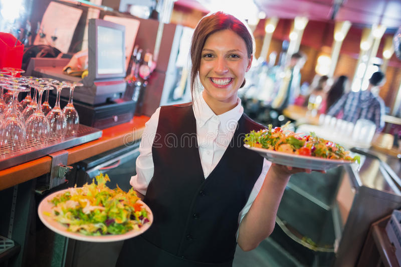 Jolie barmaid tenant des plats des salades photos stock