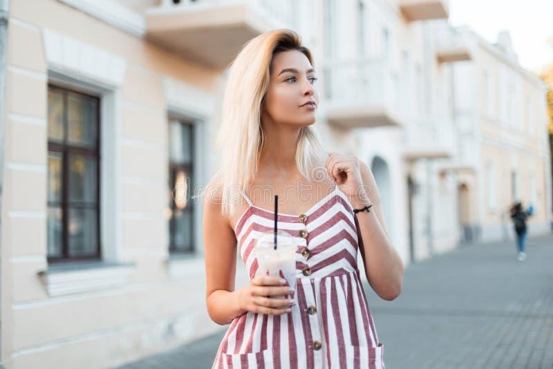 Jolie belle jeune femme blonde heureuse dans une robe rayée rose à la mode avec une boisson au lait douce près d'un bâtiment dans photo libre de droits