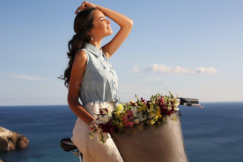 Jolie bicyclette de sourire d'équitation de fille le long de la côte photos libres de droits