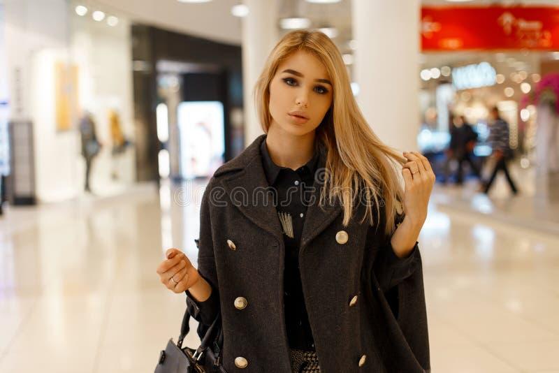 Jolie blonde à la mode urbaine de jeune femme dans un manteau élégant dans un chemisier noir dans le pantalon de plaid avec un sa photo libre de droits