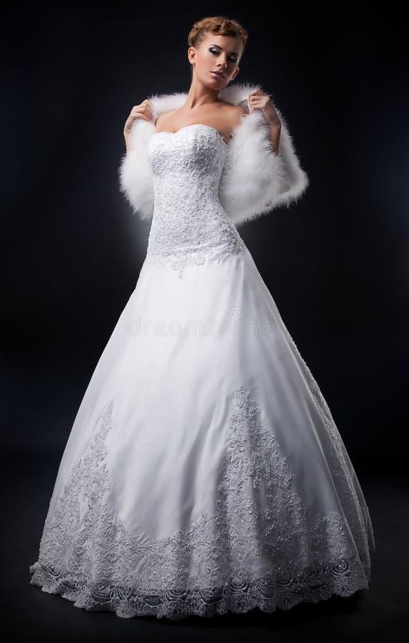 Jolie blonde spectaculaire de mariée dans le blanc nuptial photographie stock