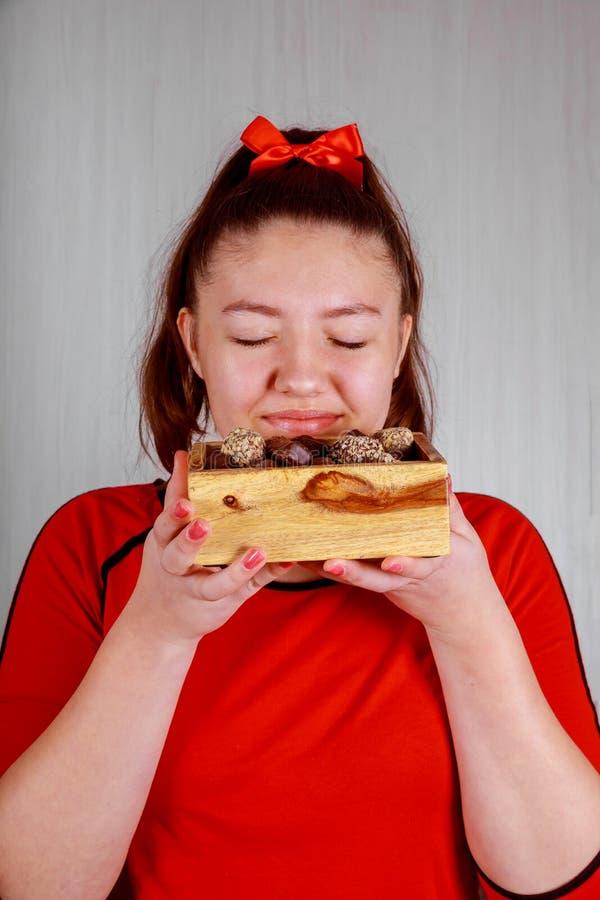 Jolie boîte heureuse d'ouverture de fille avec des bonbons au chocolat l'anniversaire et le Saint Valentin photographie stock