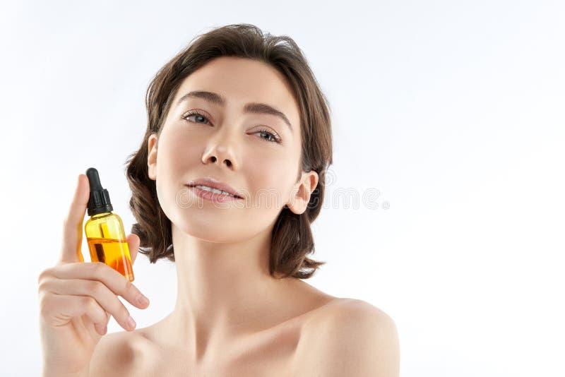 Jolie bouteille se tenante femelle sensuelle avec de l'huile photos stock