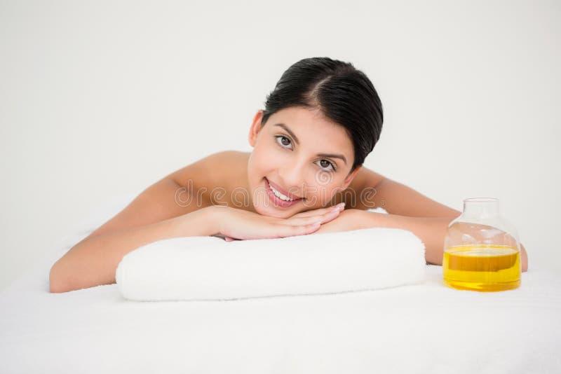 Jolie brune appréciant un massage souriant à l'appareil-photo images libres de droits