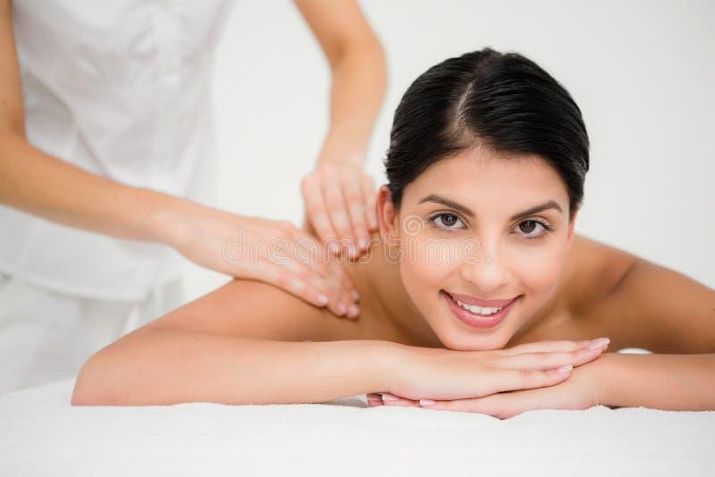 Jolie brune appréciant un massage souriant à l'appareil-photo image libre de droits