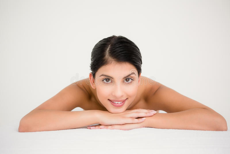 Jolie brune appréciant un massage souriant à l'appareil-photo image stock