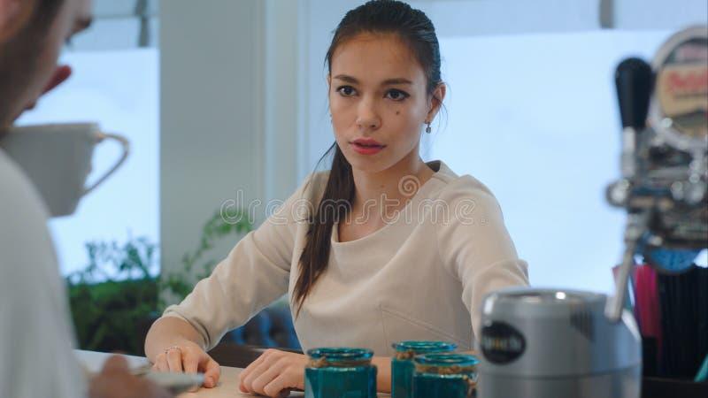 Jolie brune non heureuse avec du son café et le donner de nouveau au serveur photos libres de droits