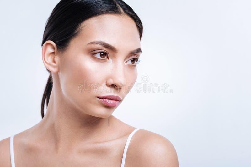 Jolie brune posant avec un regard de intimidation photo stock
