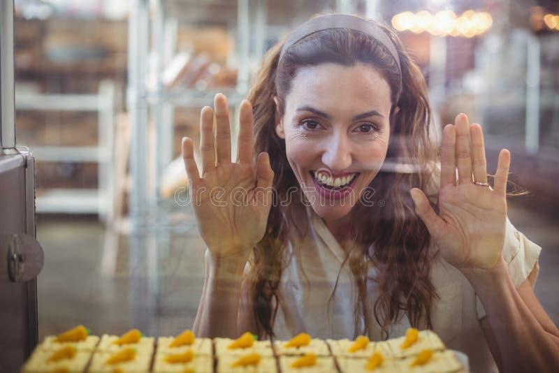 Download Jolie Brune Regardant Des Pâtisseries Par Le Verre Image stock - Image du heureux, rester: 56486043