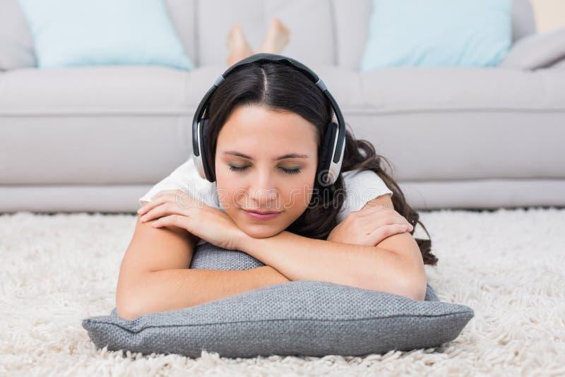 Jolie brune se trouvant sur la couverture écoutant la musique photographie stock libre de droits