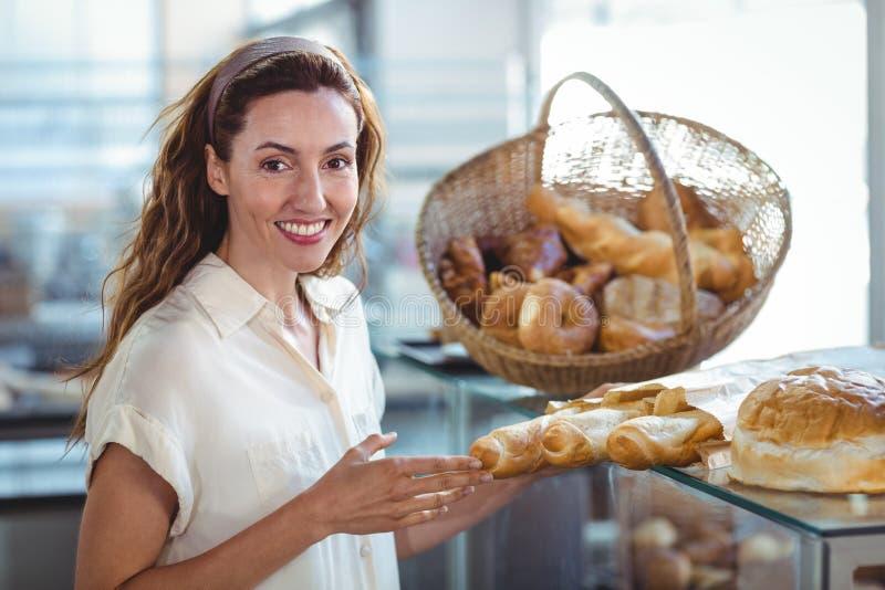 Download Jolie Brune Souriant à L'appareil-photo Et Tenant La Miche De Pain Photo stock - Image du café, restaurant: 56486790