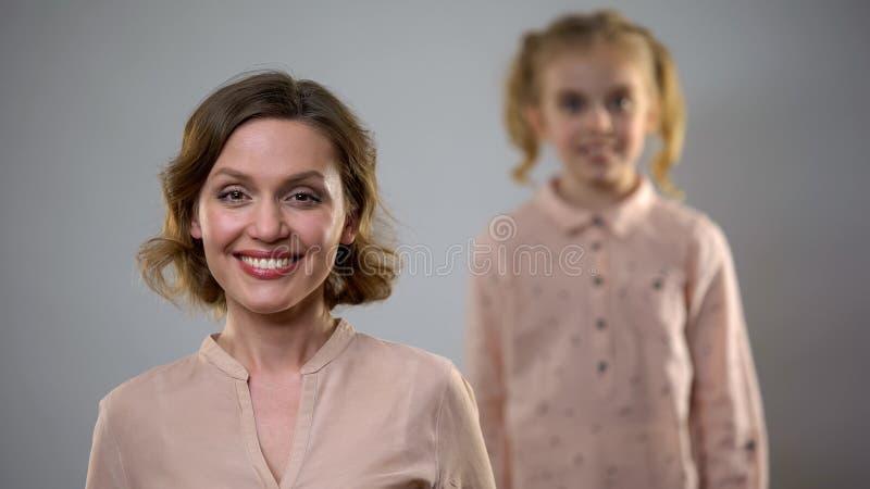 Jolie cam?ra de sourire de jeune dame avec la fille blonde se tenant derri?re, connexion photo libre de droits