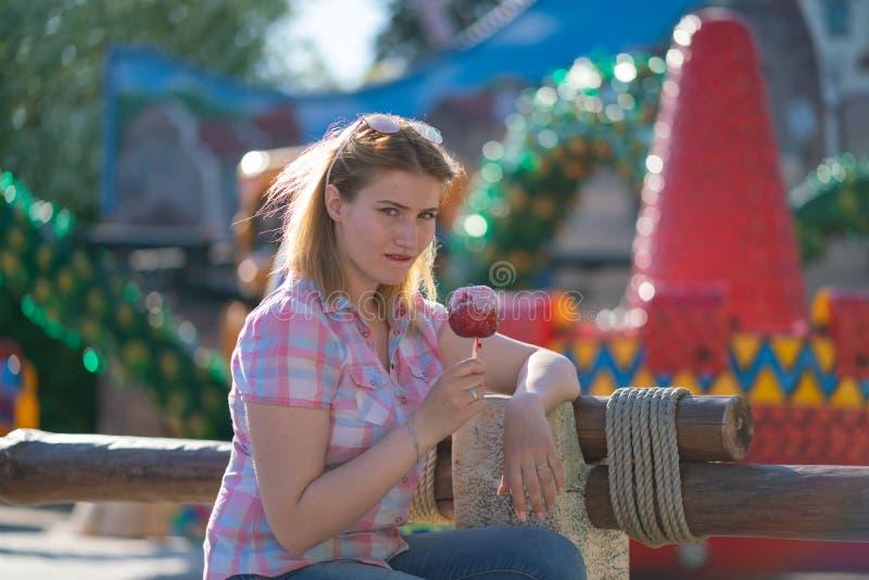 Jolie consommation de jeune femme et pomme de caramel rouge acérée en parc pendant le jour ensoleillé photo stock