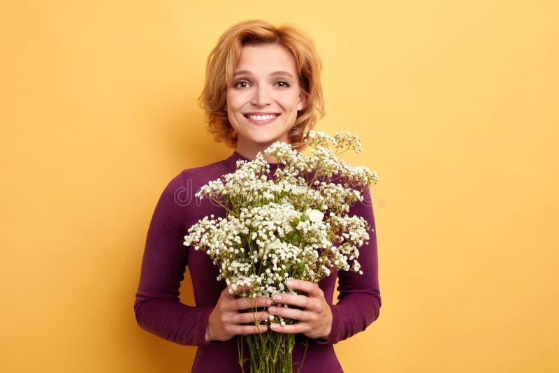 Jolie dame avec du charme attirante avec les cheveux blonds tenant un groupe de fleurs sauvages photographie stock libre de droits