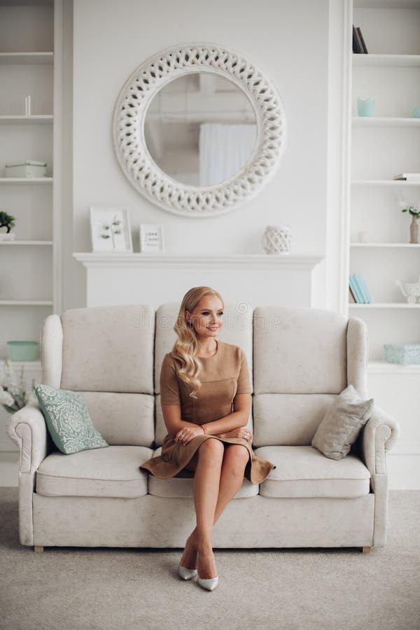 Jolie dame magnifique reposant et tenant des mains sur des genoux image stock