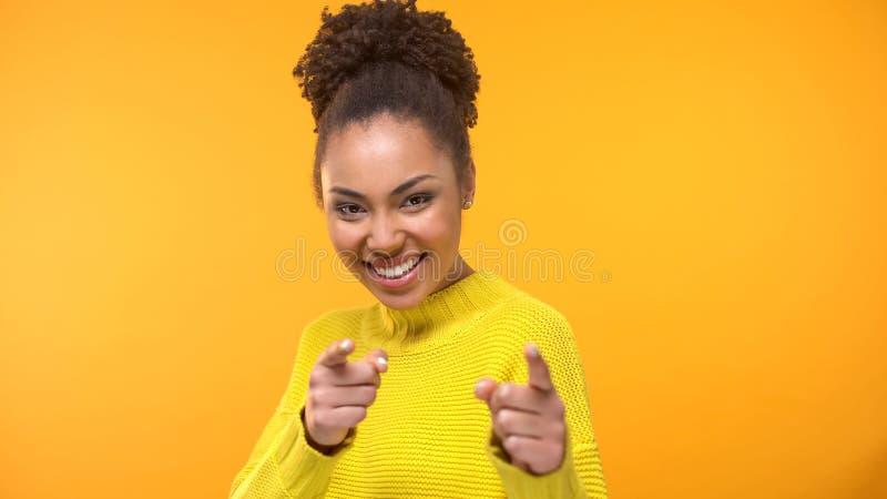 Jolie dame noire de sourire montrant je vous choisis geste dans la cam?ra, fin  photo stock