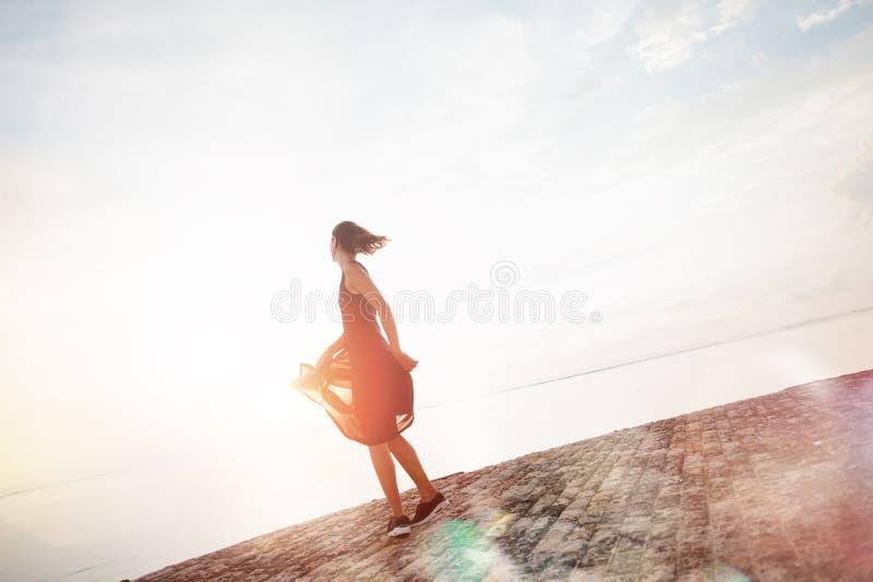 Jolie danse de femme au lever de soleil près de l'océan photographie stock
