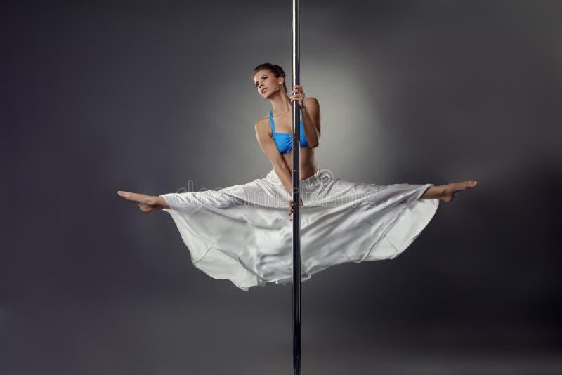 Jolie danse flexible de fille sur le poteau dans le studio photos stock