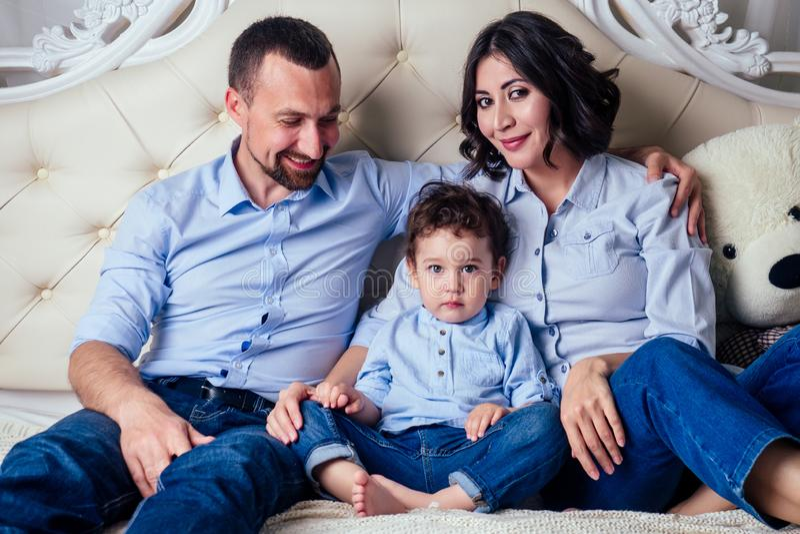 Jolie famille belle mère petit fils et père se reposer et passer du temps ensemble sur le lit dans la chambre image stock