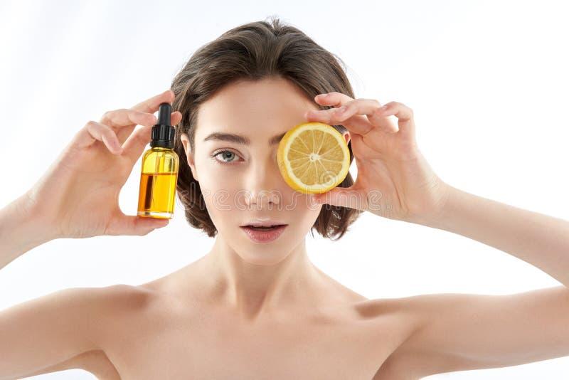 Jolie femelle nue avec la bouteille de citron et de pétrole photographie stock
