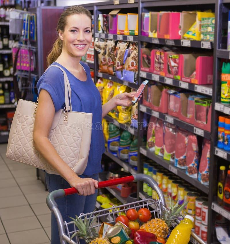 Download Jolie Femme à L'aide De Son Smartphone Devant Le Bas-côté De Produit Image stock - Image du épicerie, personne: 56489009