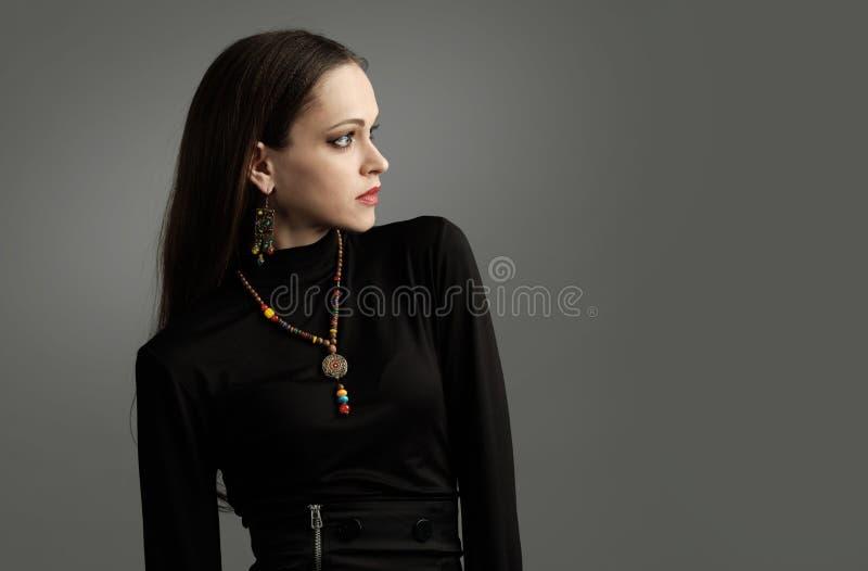 Jolie femme à la mode portant les vêtements et les bijoux noirs photographie stock libre de droits