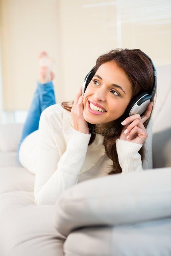Jolie femme écoutant avec des écouteurs la musique se trouvant sur le divan photographie stock libre de droits