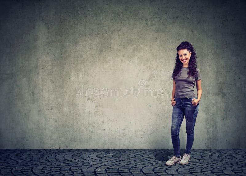 Jolie femme élégante contre le mur gris image stock