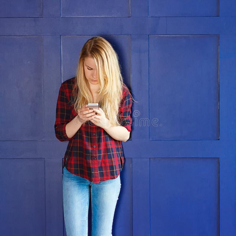 Jolie femme appelle quelqu'un par le téléphone portable tout en souriant images stock