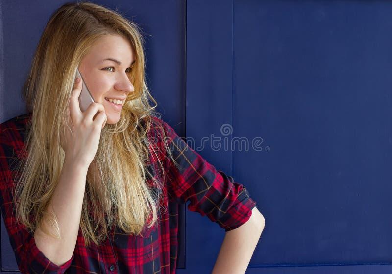 Jolie femme appelle quelqu'un par le téléphone portable tout en souriant image libre de droits