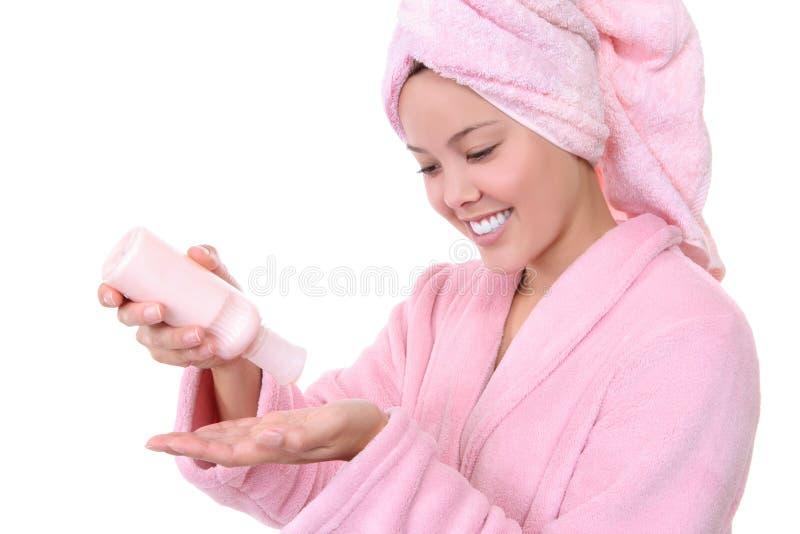 Jolie femme appliquant la lotion photographie stock