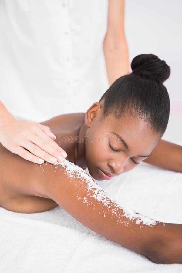 Jolie femme appréciant un massage d'exfoliation images stock