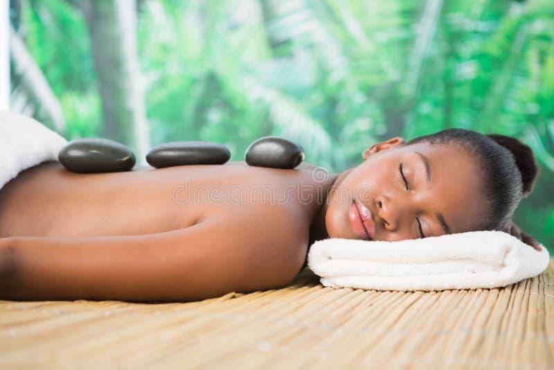 Jolie femme appréciant un massage en pierre chaud photo stock