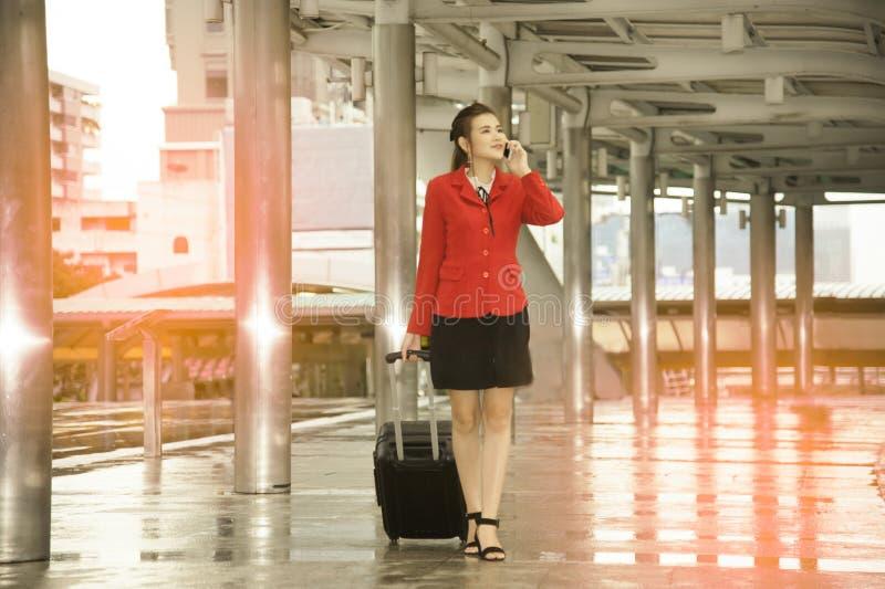 Jolie femme asiatique d'affaires avec le bagage et le téléphone intelligent d'utilisation photos stock