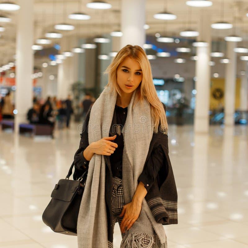 Jolie femme attirante à la mode dans un manteau élégant gris avec une écharpe à la mode de cru avec un sac à main noir en cuir photo stock