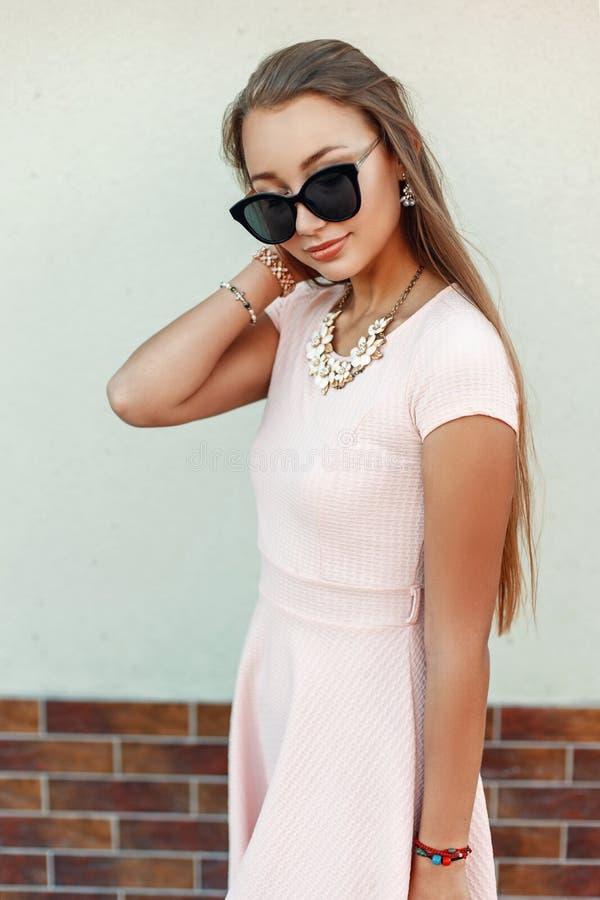 Jolie femme avec des lunettes de soleil dans une robe rose près du mur vert images stock