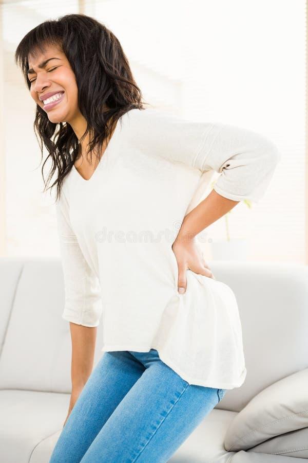 Jolie femme avec douleurs de dos photos libres de droits