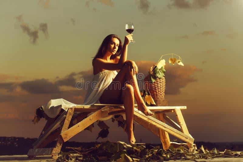 Jolie femme avec du vin au-dessus du ciel photographie stock