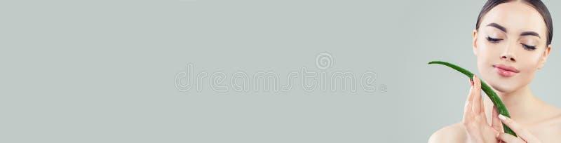 Jolie femme avec la peau claire tenant la feuille de Vera d'aloès dans des ses mains, concept de soins de la peau images libres de droits