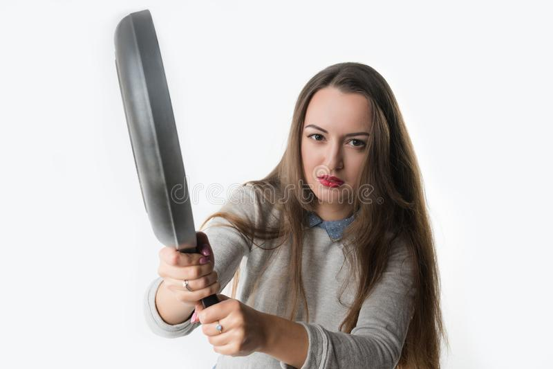 Jolie femme avec la rage, l'umbragem, l'insulte sur son visage et la poêle image libre de droits