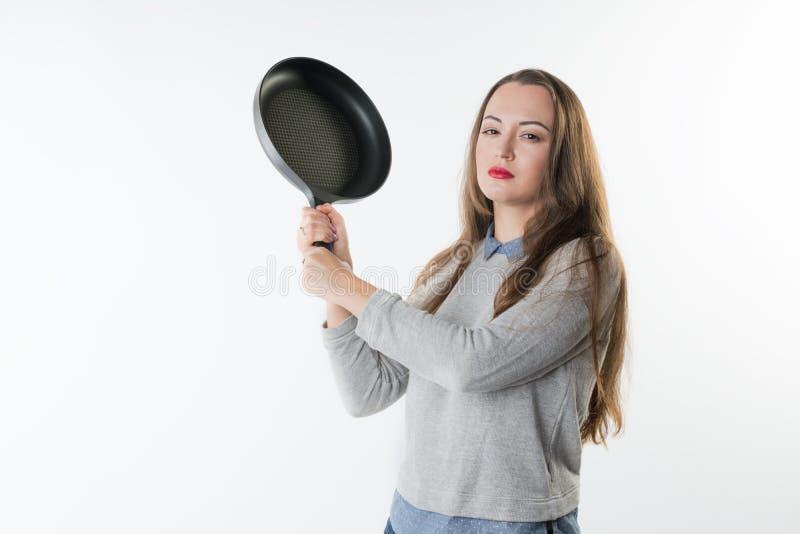 Jolie femme avec la rage, l'umbragem, l'insulte sur son visage et la poêle photographie stock libre de droits