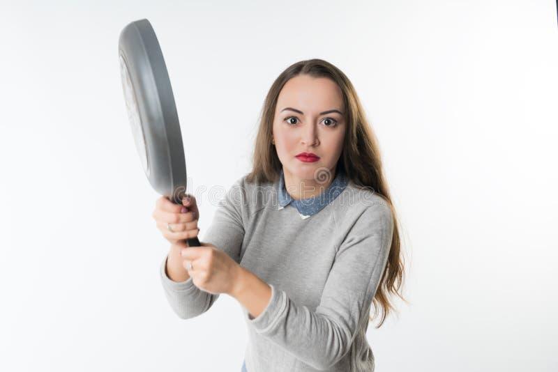Jolie femme avec la rage, l'umbragem, l'insulte sur son visage et la poêle photo stock